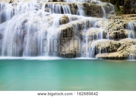 Waterfall cascading over a shelf of rocks into a quiet pool below in a long exposure nature background with veils of white water