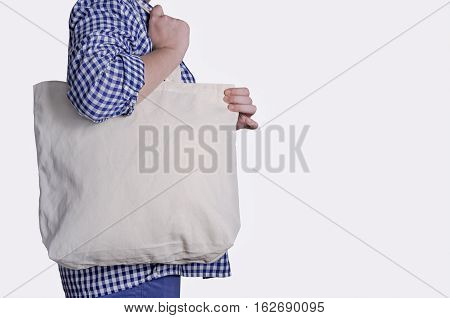 Mock-up. Girl is holding blank cotton tote bag isolated on white background. Handmade eco shopping bag for girls.