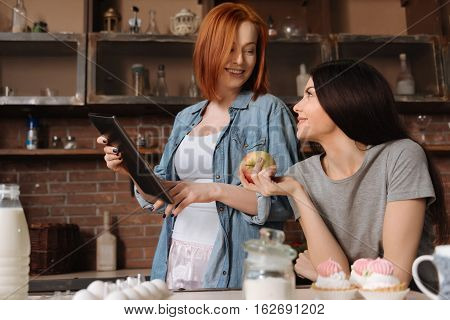 Take an apple. Positive delighted brunette holding big apple in right hand leaning elbows on the table while looking at her friend