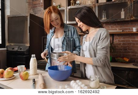 Add some ingredients. Positive delighted females wearing casual clothes sieving flour into blue plate while standing in the kitchen