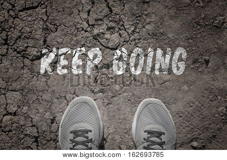 Sneakers on dry land with the text: Keep going