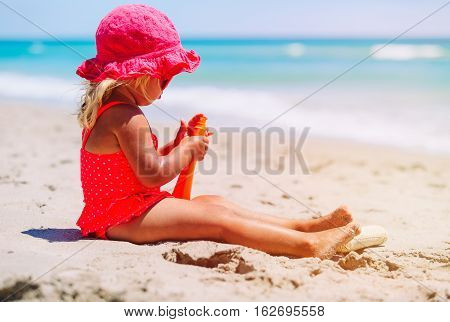 sun protection concept - little girl with suncream at tropical beach