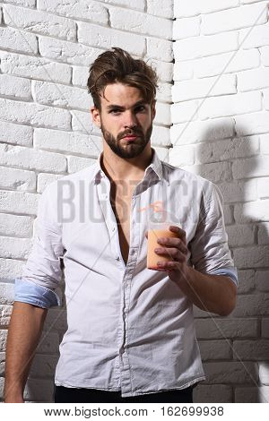 young handsome bearded sexy macho man with stylish beard in white unbuttoned shirt holding glass of nonalcoholic cocktail on brick wall background poster
