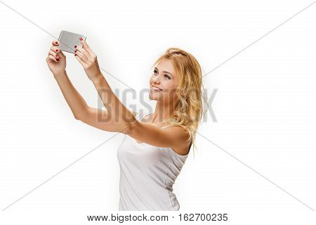 Portrait of beautiful smiling girl making selfie with modern cell phone in hands on white background.