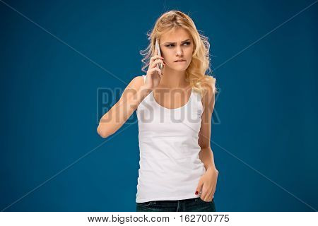 Portrait of beautiful serious girl with modern cell phone in hands on blue background.