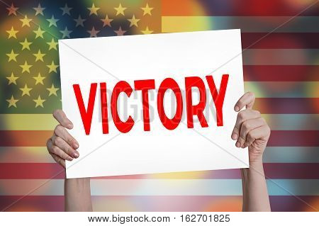 Victory placard in hand with bokeh background