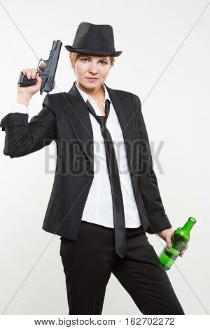 beautiful girl gangster holding a gun. Classic suit and hat. isolated on white background. red nail polish