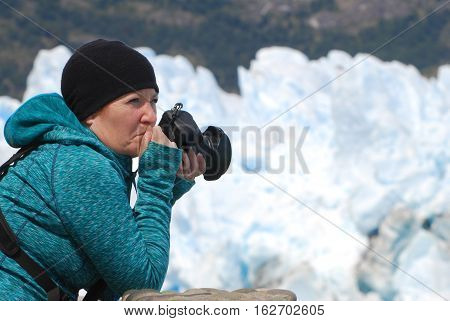 Photographer holding camera looking in awe at Perito Moreno Glacier in Los Glaciares National Park Argentina.