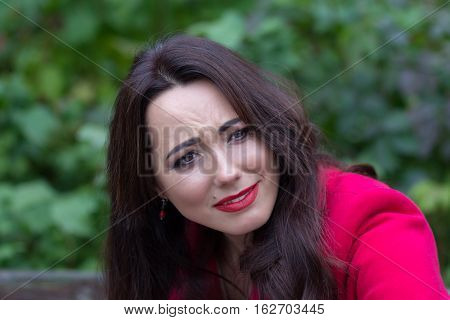 Portrait of expressive woman in a red coat. People