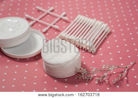 facials skin care. cotton pads and buds on the pink backgroung