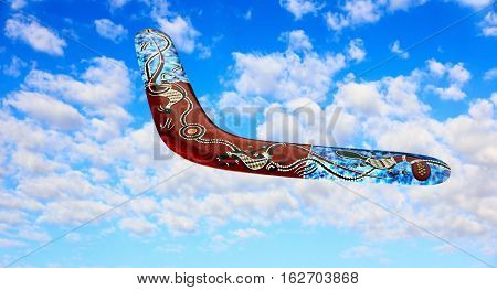 Multicolored australian boomerang flies in sky against of pure white clouds.