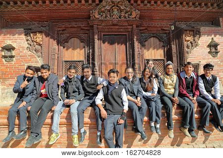 PATAN, NEPAL - DECEMBER 21, 2014: Nepalese students posing in front of a temple at Durbar Square