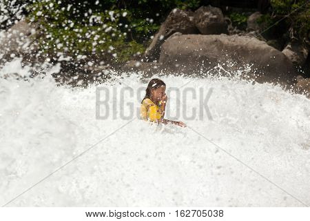 Little girl is in the middle of smashing big wave