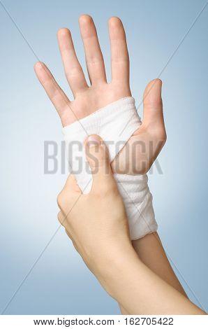 Injured painful female hand with white bandage