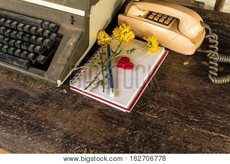 Vintage typewriter, old classic telephone ,white book ,red heart ,pencil and dry chrysanthemum flower on old wooden touch-up in still life concept,dark tone