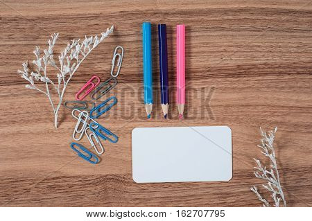 Wooden office table with different stationery top view. Office worker workplace with pencils paper stapler and staples