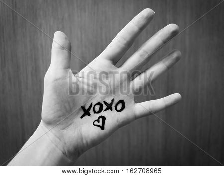 Text Xoxo and silhouette of heart on a human hand. Black and white photo. Rectangular.