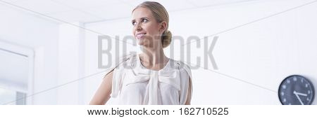 Young energetic female manager in elegant blouse in office
