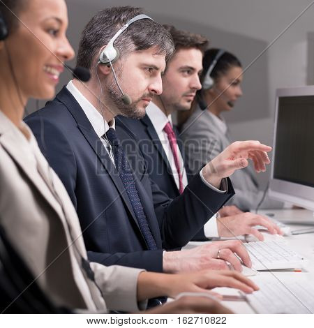 Employees of call center are engrossed in work at the desk