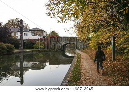 woman walking along the tow[ath of the grand union canal near berkhamsted castle in autumn in hertfordshire uk