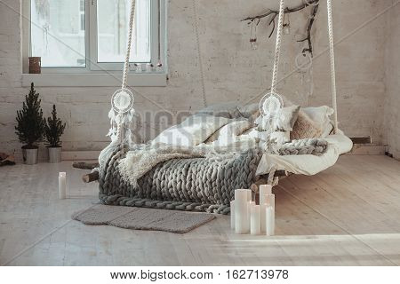 The bed suspended from the ceiling, an unusual bed. Grey big cozy blanket knit. Bed, Scandinavian style, gray plaid.