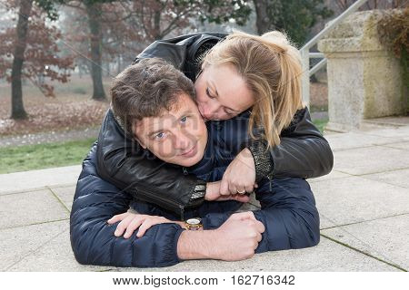 Blonde Forties Woman Kissing Her Husband Outdoor, Lying On The Park On Autumn
