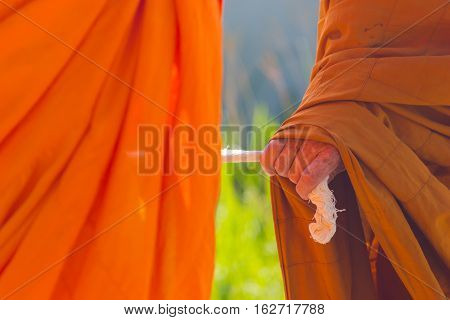 closeup hand of Thai monk holding big rope leading people to the graveyard
