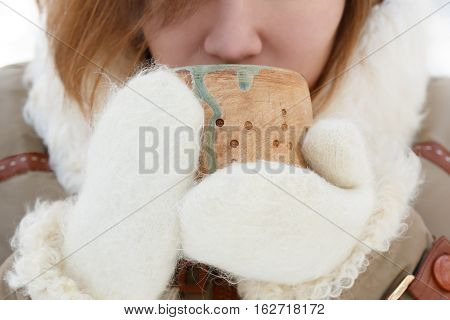Young woman in winter coat and white fluffy mittens holds pottery cup in her hands and drinks from it. Shallow dof. Focus on cup. Closeup.