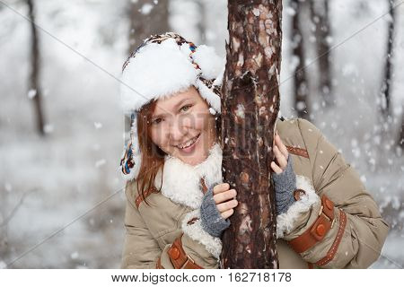 Young beautiful smiling woman in coat with white fur hat with ear flaps and grey fingerless knitted mittens hugs a tree in winter forest with falling snow around. Shallow dof. Focus on eyes.