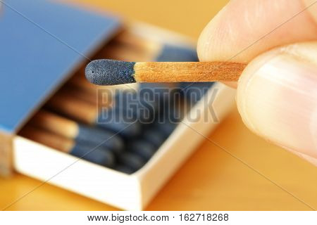Blue Matches Hand Holding with Matchbox Background