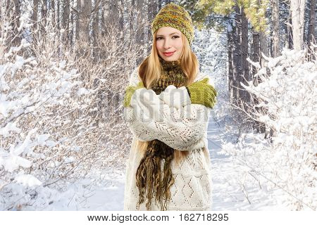 Young stylish smiling blonde woman in variegated melange knitted hat scarf with fringe mittens and long patterned white sweater stands in winter forest hugging herself.