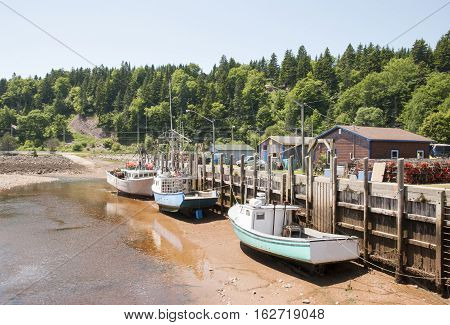 Boats are resting during the low tide in high tide famous St. Martins village (New Brunswick Canada).