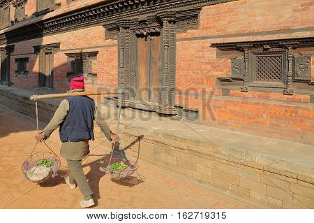 BHAKTAPUR, NEPAL: A local seller carrying vegetable in baskets at Durbar Square