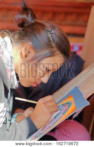 BHAKTAPUR, NEPAL - DECEMBER 29, 2014: A local artist painting a traditional Tibetan Thangka