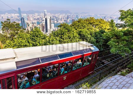 Hong Kong, China - December 10, 2016: The red Peak Tram to Victoria Peak, the highest peak of Hong Kong island. Tourist tram with panoramic city skyline on background. Sunny day.