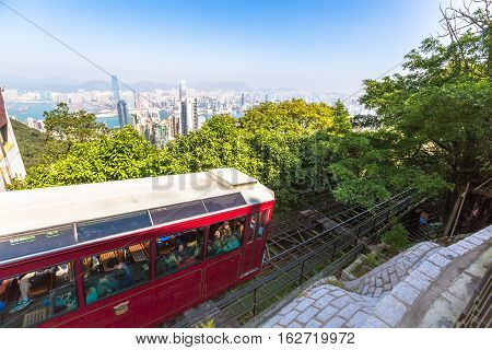 Hong Kong, China - December 10, 2016: The red Peak Tram to Victoria Peak, the highest peak of Hong Kong island. Tourist tram with panoramic city skyline in the background in a sunny day.