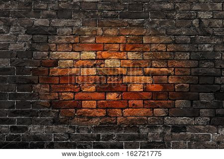 Old brick wall with oval reddish spot in the center