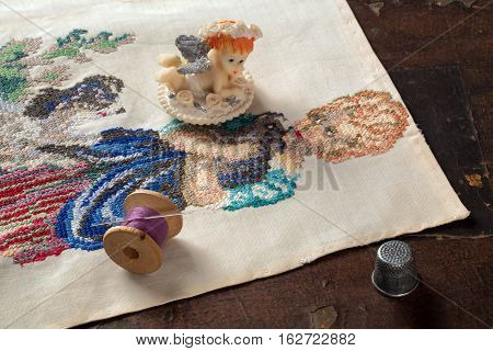 embroidery thread with a needle a thimble and a figurine of of an angel