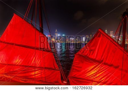 Close up of red-sail junk boat with Hong Kong island skyline background seen from the waterfront of Tsim Sha Tsui in Kowloon.