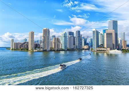 Aerial view of Miami skyscrapers with blue cloudy skywhite boat sailing next to Miami downtown
