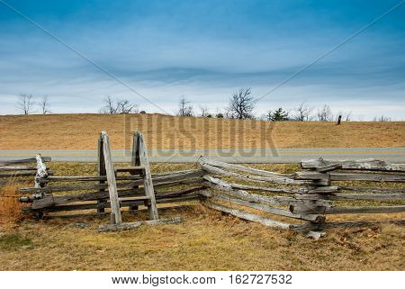 A wooden stile leads over a fence bordering the Blue Ridge Parkway
