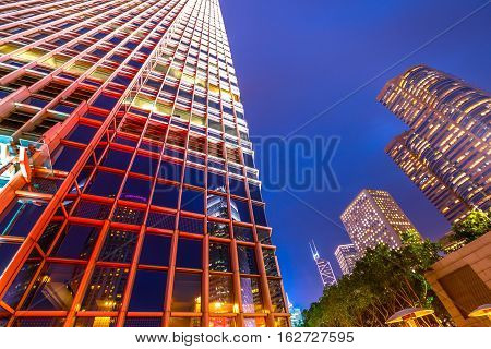 Hong Kong, China - December 6, 2016: Perspective view of Two International Finance Center glass facade or 2IFC at night, the second tallest skyscraper in Hong Kong, reflects the neighboring buildings.