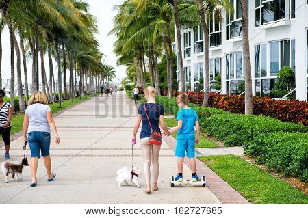 Miami USA - February 12 2016: people walkers going on road at beautiful Miami Beach with art deco architecture or hotel building and palm trees green color windy outdoor