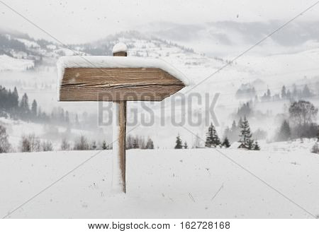 Wooden direction sign with less snow on it and with snowfall and mountains on background