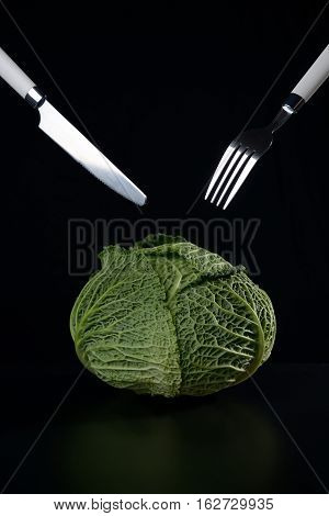 Ripe green savoy cabbage fork and spoon on a black background.