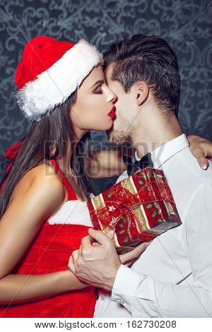 Sexy santa woman seduce young man in tux whispering Merry Christmas