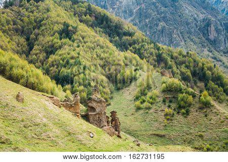 Ancient Old Stone Caves In Sioni Village, Kazbegi District, Mtskheta-Mtianeti Region, Georgia. Spring Or Summer Season. Famous Landmarks And Places In Kazbegi District.