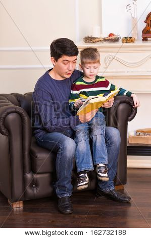 Father and son reading story book together.