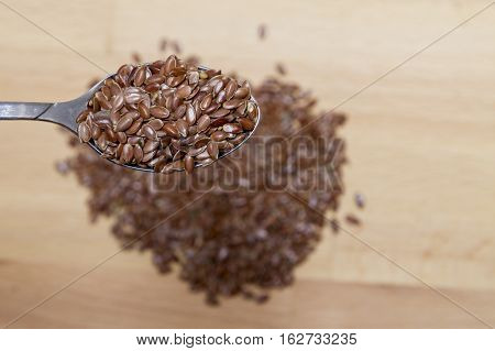 Top View Of Organic Linseed In A Spoon On Wood Background.
