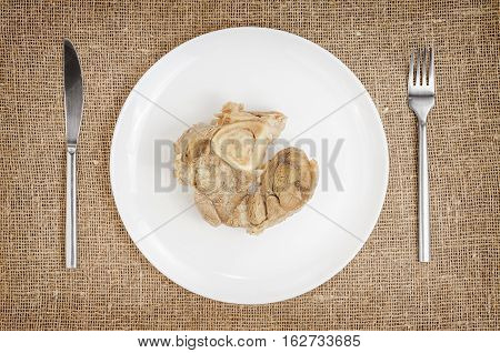 Linen background with boiled pork on plate with knife and fork. Animal food.